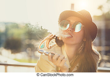 Pretty young girl vape popular ecig gadget, vaping device. Happy brunette vaper girl with e-cig. Portrait of smoker female model with electronic cigarette vaporizer. Ejuice vaping with fruit flavor liquid