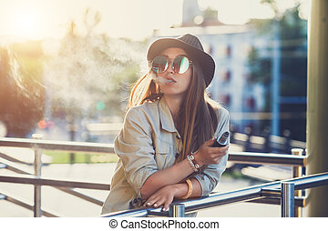 Pretty young hipster woman in black hat vape ecig, vaping ...