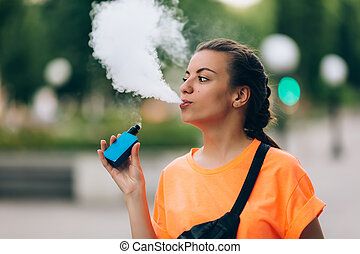 Pretty young hipster woman vape ecig, vaping device at the ...