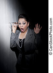Pretty young Hispanic woman using glass to eavesdrop -...