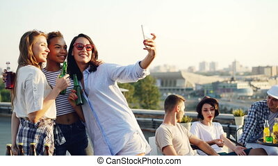 Pretty young ladies are taking selfie with bottles using smartphone during party on roof while their friends are chatting in background. Modern technology and fun concept.