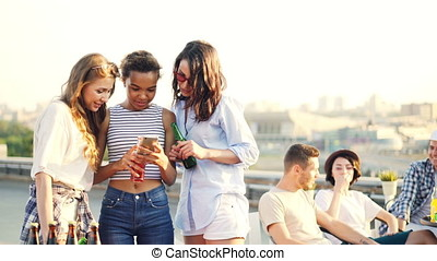 Pretty young ladies are using smartphone looking at screen and talking standing on roof with bottles enjoying party. Modern technology, leisure and fun concept.