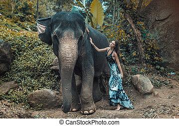Pretty young lady cuddling an elephant