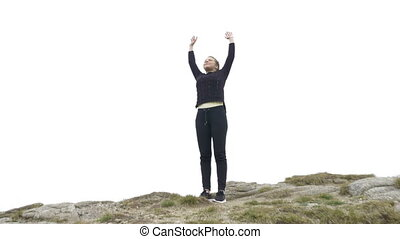 Pretty young lady doing yoga exercises on the mountain high raising arms while she taking a deep breath