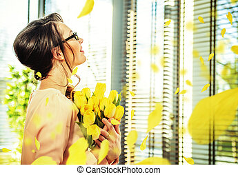 Pretty young lady holding a bouquet of tulips