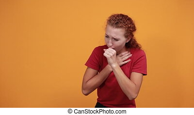 Pretty young lady in red shirt cough, looking sickness isolated on orange background in studio. People sincere emotions, health concept.