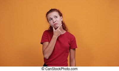 Pretty young lady in red shirt thinking about issue, keeping hand on chin isolated on orange background in studio. People sincere emotions, health concept.