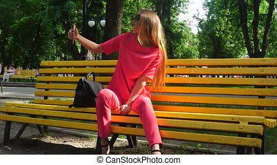 Pretty young lady in red suit makes selfie on a bench at the park