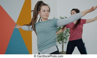 Pretty young lady in sports clothing is exercising indoors in yoga club focused on asanas physical exercises enjoying healthy occupation. Youth and health concept.