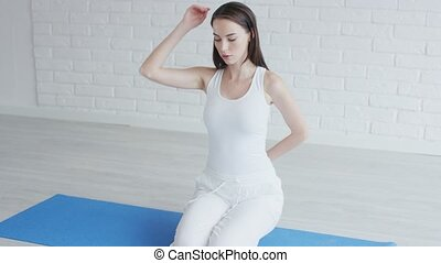 Pretty young lady in sportswear doing yoga or fitness ...