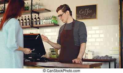 Pretty young lady is buying takeaway coffe in coffee-shop and paying with smartphone making contactless payment. Modern technology and banking concept.