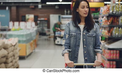 Pretty young lady is walking through aisle in supermarket...