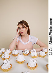 Pretty young lady posing while sitting near cupcakes on table