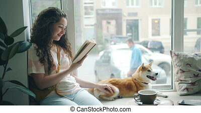 Pretty young lady reading novel in cafe on window sill and...