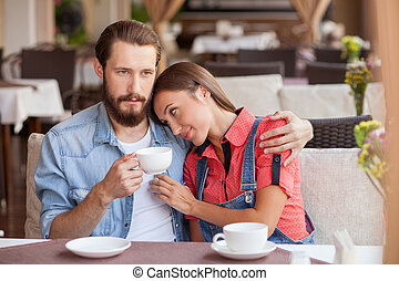 Pretty young loving couple is resting in cafe