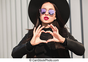 Pretty young model in glasses and hat making a heart shape with her hands