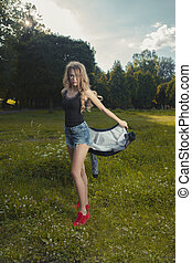 Pretty young model wearing lace shirt and torn jeans shorts and poaing in the park