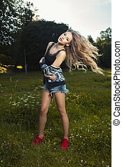 Pretty young model with long hair in wind posing at the park