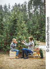 Pretty young mother and the son in gray sweaters decorating a Christmas tree in winter forest outdoors. Boy is drinking hot tea and sitting on wooden sledge with present boxes under the tree