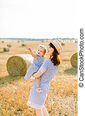 Pretty young mother in straw hat and striped dress holding on hands her cute little baby girl, looking away on the sky, walking in summer field with wheat hay bales on the background
