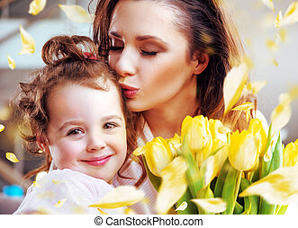 Pretty young mother kissing daughter