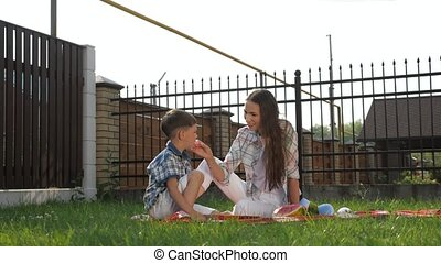 pretty young mother with loose dark hair sits and feeds son...