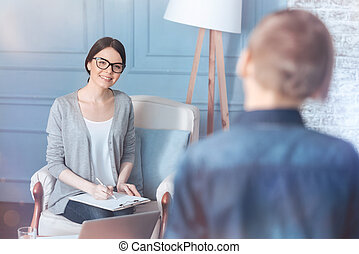 Pretty young psychotherapist meeting teenage patient in office