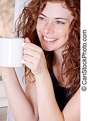pretty young redhead woman with freckles and coffe