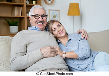 Pretty young smiling woman and her happy senior father relaxing on couch at home