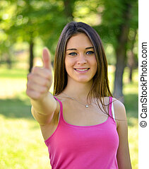 Pretty young smiling woman showing gesture that everything is ok