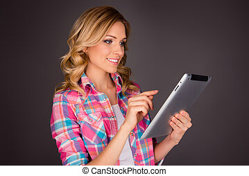 Pretty young smiling woman touching screen of tablet