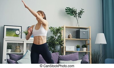 Pretty young sportswoman practising at home raising arms and...