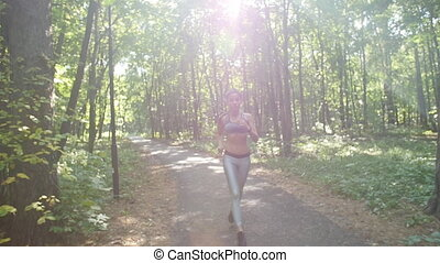 Pretty young sporty woman jogging at park or forest