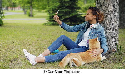 Pretty young woman African American student is making video call using smartphone and petting her dog sitting on lawn in park. Modern communication and pets concept.