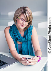 Pretty, young woman at an office, using a laptop and her smartphone