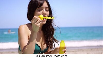 Pretty young woman blowing bubbles on a beach - Pretty young...