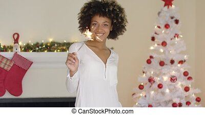 Pretty young woman burning a Christmas sparkler