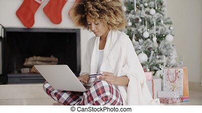 Pretty young woman buying Christmas gifts online
