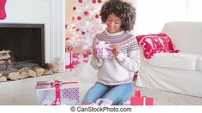 Pretty young woman checking her Christmas gifts
