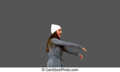 Pretty young woman cheering on grey background