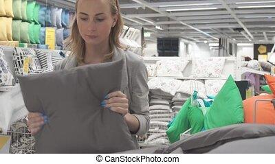 Pretty, young woman choosing a pillow