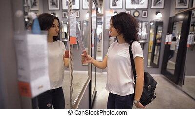 Pretty, young woman choosing a wardrobe in shop - Pretty,...