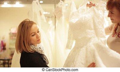 pretty young woman choosing a wedding dress. shop assistant...