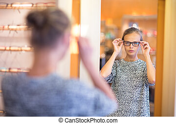 Pretty, young woman choosing new glasses frames in an optician store