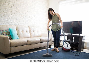 Pretty young woman cleaning her house