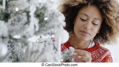 Pretty young woman decorating a Christmas tree
