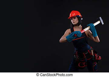 Pretty young woman doing repairs at home. Portrait of a female construction worker. Building, repair concept.