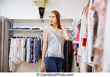 Pretty young woman doing shopping in clothing store
