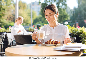 Pretty young woman drinking latte in cafe - Delicious...