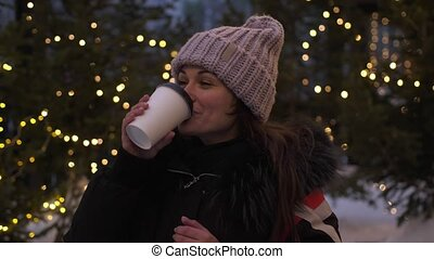 Pretty young woman drinks hot coffee outside at Christmas market. Cute girl in winter, drinking hot coffee or chocolate beside decorated with lights tree. slow motion